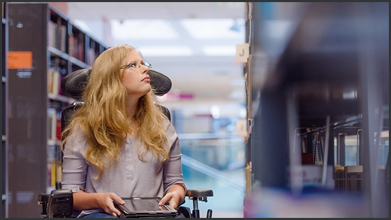 Student in a wheelchair, with a tablet computer, looks at library shelves