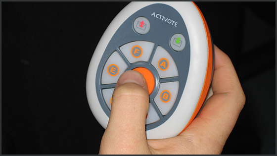 Student's hand holding a voting device called a clicker, the thumb poised to vote