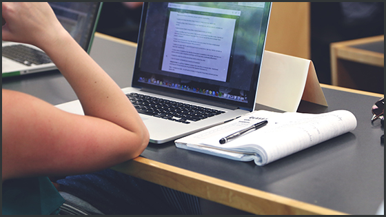 Student works at a desk with a laptop and notebook nearby