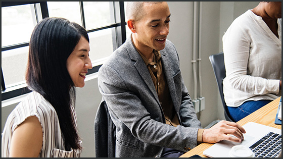 a young man and woman working on a laptop together