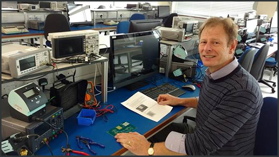 An academic sits at a bench in an electronics laboratory