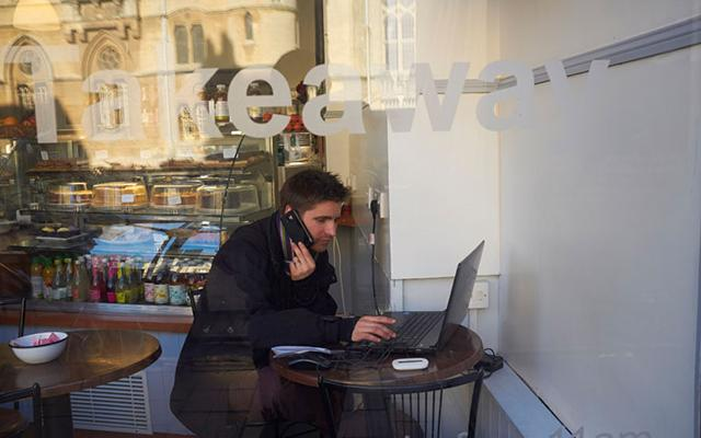 Lecturer on the telephone, sitting inside a cafe with laptop open in front of him, reflected in the cafe windows are Oxford college buildings