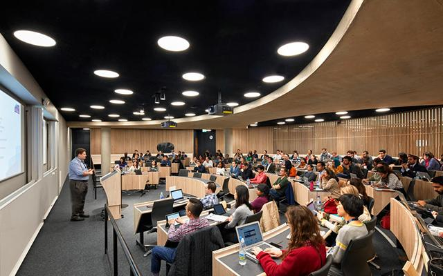 A lecturer stands at the front of packed lecture hall, students sit at curved desks most with laptops or tablets