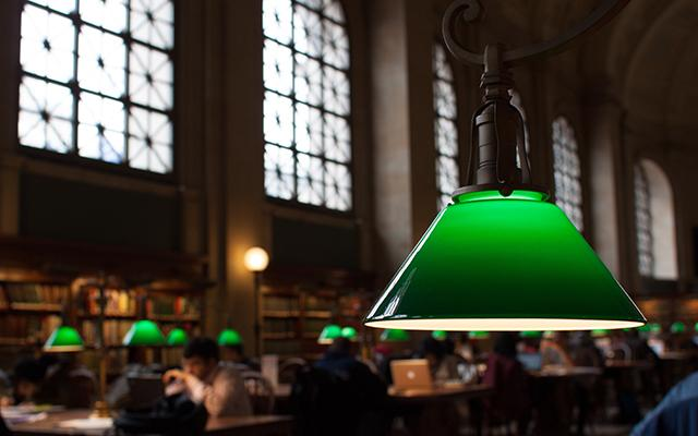 Reading lamp in the foreground, in the background students work on laptops studying in a library