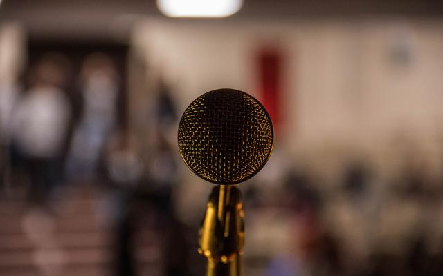 close-up of a microphone in front of a blurry background