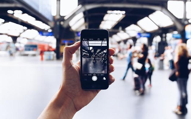 A hand holding a cell phone filming a blurred scene at an airport