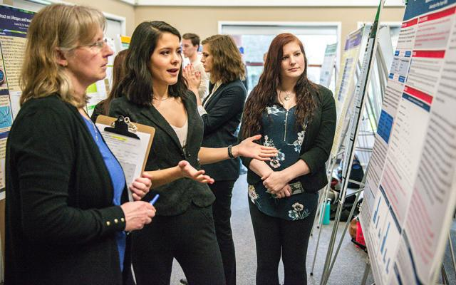 a young woman explaining her research poster