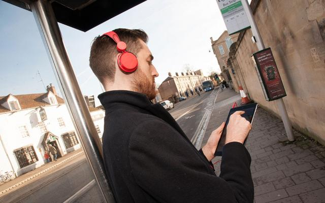 A male student at a bus stop watches a lecture on his tablet