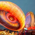 Fairground rides, blurred lights, sky at twilight