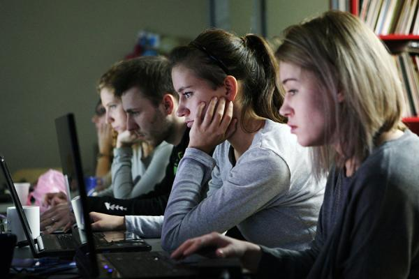A row of five students work at laptops