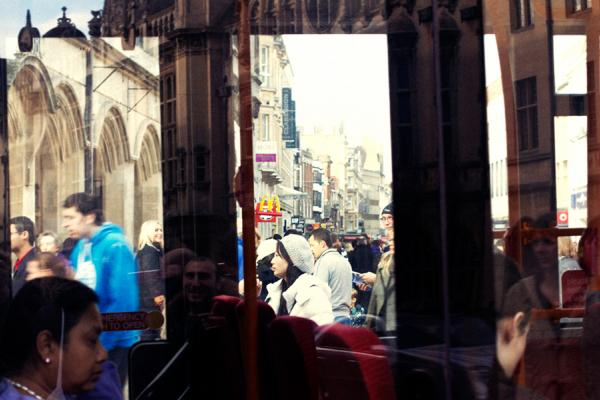 Shoppers (and reflections of buildings) in Oxford seen through the windows of a bus full of passengers