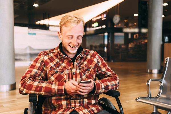 Student in a wheelchair checks his smartphone