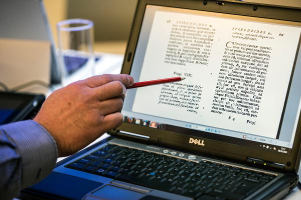 Lecturer points to an image on a laptop screen of a folio printed in Latin