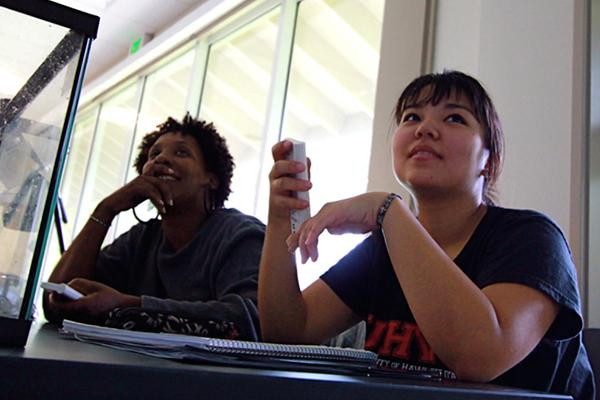 Two students with clickers in the hand wait to vote on the next question