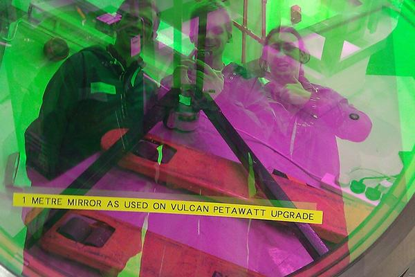 Three smiling students are reflected in a bright green diffraction grating, the middle one holds a phone to take their selfie, another holds his thumbs up