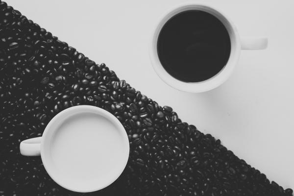 coffee cup on white background and milk cup on black background (coffee beans)