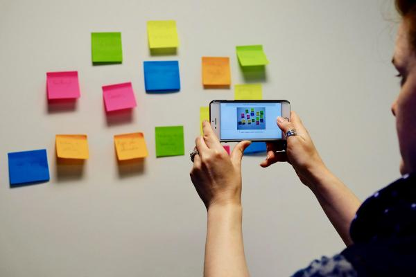 a female student taking a photo of her sticky notes with her phone