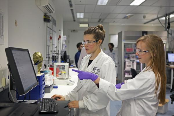 two female students looking and pointing at a computer screen inside a laboratory
