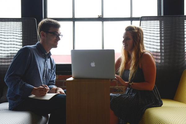 a female student and a man talking over an open laptop