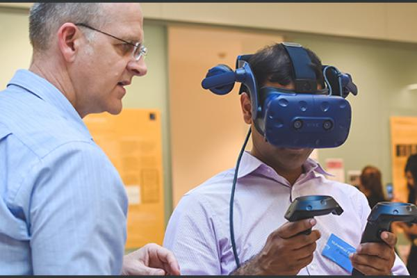 man wearing VR glasses facilitated by another man