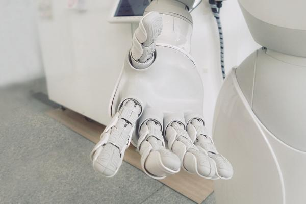 a robot's hand inviting viewer to take it