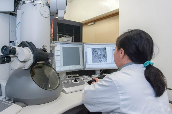 Woman sitting next to a microscope using a computer to see microscope images