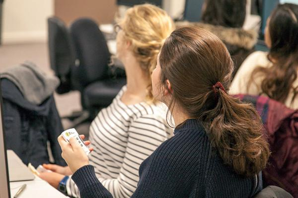 Class of students with polling handsets watching a lecturer