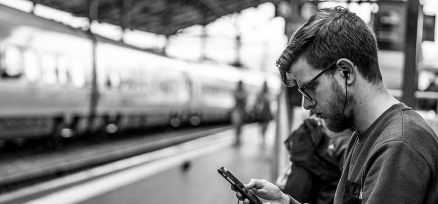 a man with glasses on train platform listening to podcast on mobile phone black and white