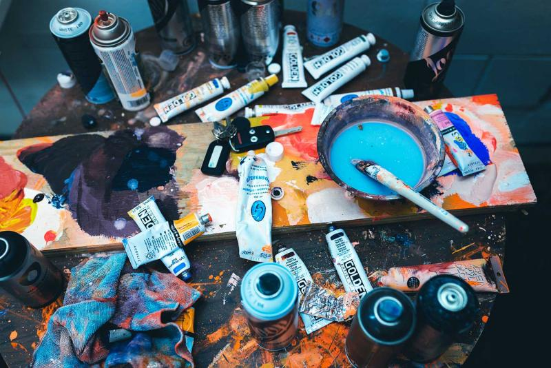 paint tubes, spray cans, paint brushes and other art material scattered over a table
