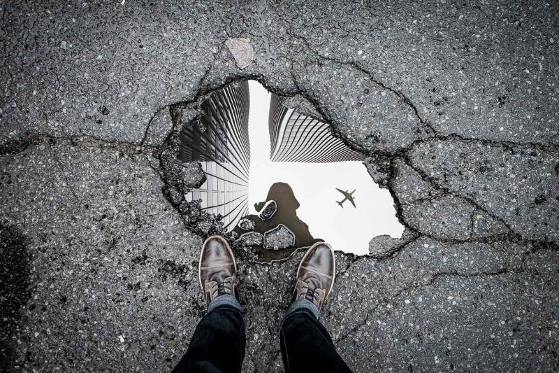 a puddle reflecting the photographer, skyscrapers and a plane