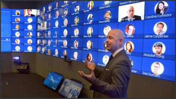 A man standing in front of a wall covered with screens