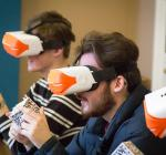 Three Oxford students wearing Virtual Reality headsets and handling QR cubes