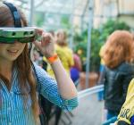 A student looks through VR goggles in a large greenhouse, while a researcher watches